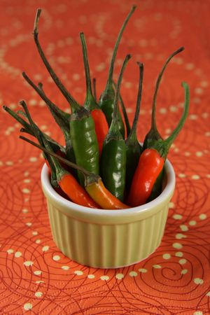 Red and green serrano peppers in a small ramekin Stock Photo