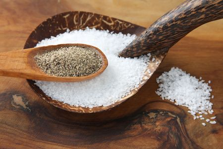 Salt and pepper in wooden spoons