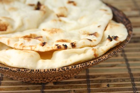 naan: Two slices of naan bread in wooden bowl
