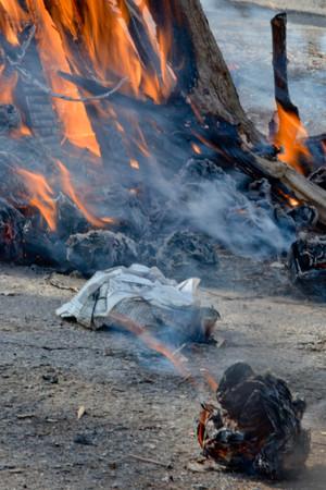 Fin de las vacaciones eslavas del invierno. Se está quemando una gran muñeca de felpa de paja. El humo negro es visible Foto de archivo