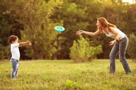 Image of family, mother and son playing frisbeel in the park.  Stock Photo
