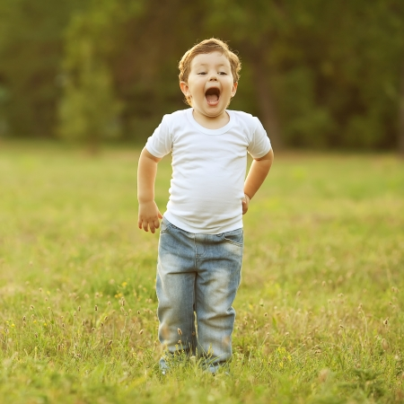 happy baby boy with brown hair having fun in the park, shouting and singing a song. outdoor shot