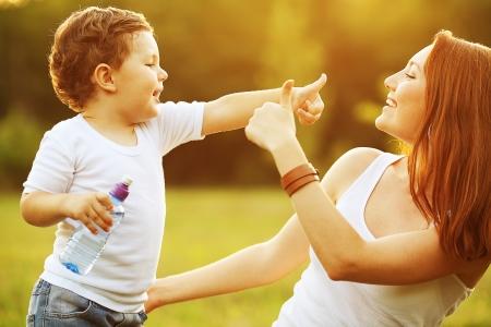 家庭: 幸福的家庭樂趣。男嬰與棕色捲髮和他的母親用生薑頭髮出了對方的拇指。戶外拍攝