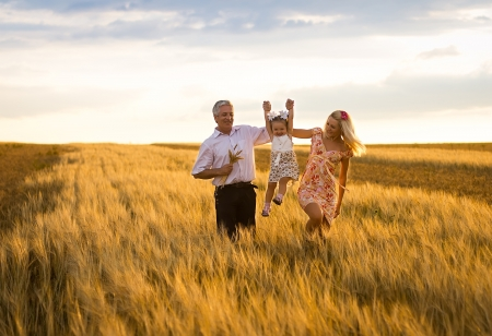 autumn family: mother, daughter and grandpa with a bouquet of wheat in the sunlight having fun