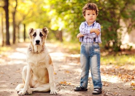 dog days: chico lindo que juega con su perro en el parque del otoño