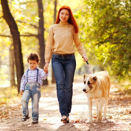happy family having fun in the park  Mother sitting with black dog  cane corso  and her son running away