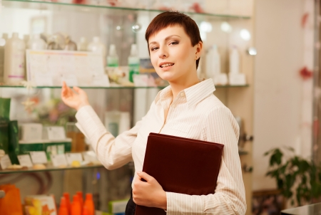 The girl-seller shows to the visitor assortment of goods Stock Photo