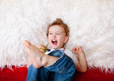 2 persons only: Portrait of young boy lying on sofa at home, looking at camera, smiling