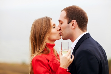 young couple drinking champagne and kissing photo