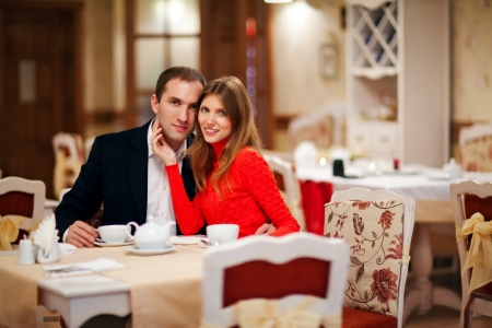 Romantic young couple sitting in a restaurant holding their hands photo