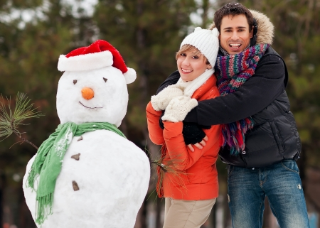 couple in love in the winter, sculpted snowman Stock Photo