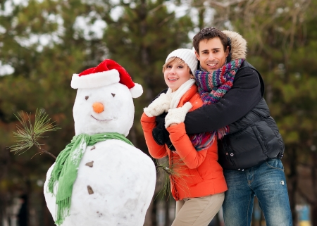 couple in love in the winter, sculpted snowman photo