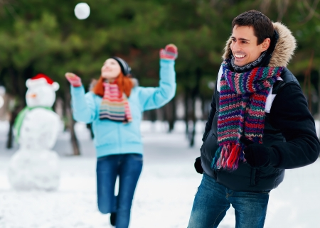 Snowball fight  Winter couple having fun playing in snow outdoors  Young joyful happy multi-racial couple  photo