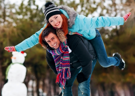 Smiling young man piggybacking his pretty girlfriend in winter