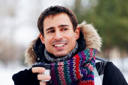 young attractive man drinking tea outside in winter time, close up portrait Stock Photo