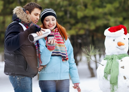 thermos: Portrait of happy couple going to drink hot tea on winter day