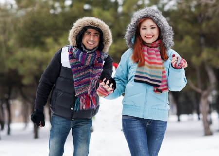 Winter couple having fun playing in snow outdoors  Young joyful happy multi-racial couple