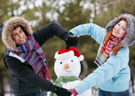 palle di neve: Giovani coppie che hanno Snowball Fight In giardino