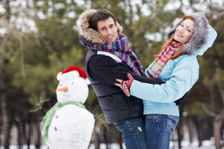 Winter couple having fun playing in snow outdoors.  photo