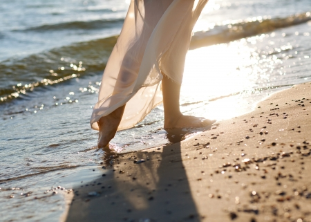 A girl walking on a beach Stock Photo