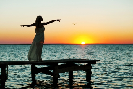 happiness people silhouette on the sunset: beautiful girl standing on a bridge at sunset ,silhuette Stock Photo
