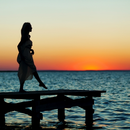 beautiful girl standing on a bridge at sunset photo
