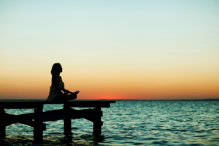 beautiful girl standing on a bridge at sunset photo