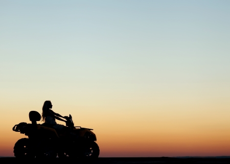 girl sitting behind the wheel of the ATV at sunset Stock Photo