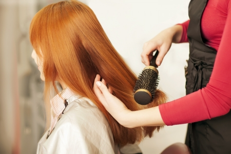 scissors hair: Beautiful young hairdresser giving a new haircut to female customer at parlor