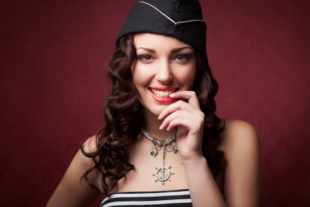 frock: beautiful woman in forage-cap and frock smiling, studio shot Stock Photo