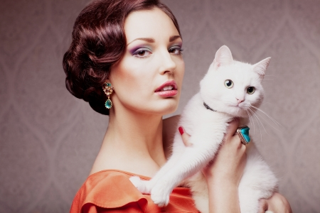 fashion model  with make up hair style and jewelry holding white cat, vintage style photo