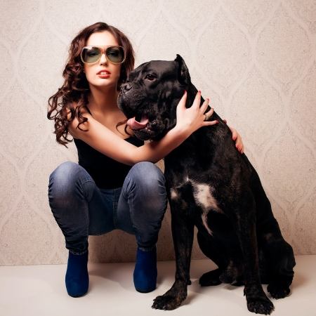 Pretty young woman smiling while embracing her cane corso photo