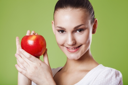 Head shot of woman holding apple Stock Photo - 18577612