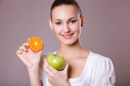 pretty girl with a green apple and half an orange
