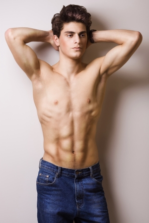 fashion brunette man with a naked torso. studio photo
