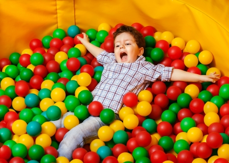 kindergarten toys: Cute kid or child playing colorful balls top view