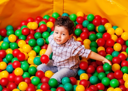 one of a kind: Cute kid or child playing colorful balls top view