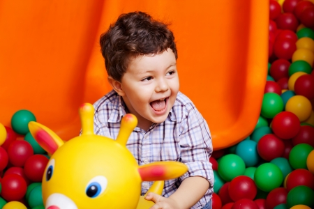 cute boy playing in colorful  balls on playground Stock Photo