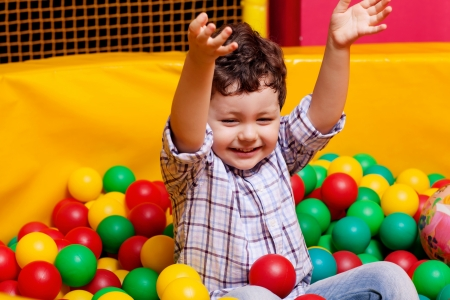 cute boy playing in colorful  balls photo