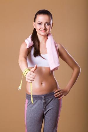 sports wear: Young happy woman in sports wear, studio shot  Stock Photo
