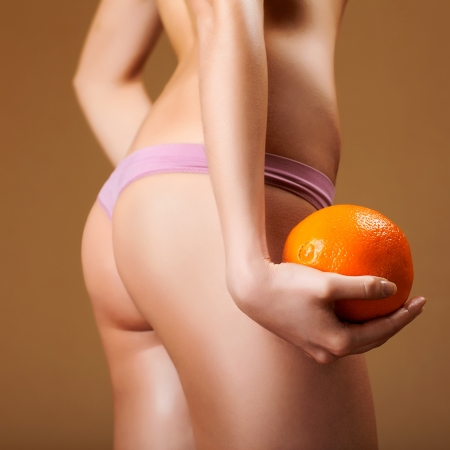 Hip, legs, abdomen and orange in hand cellulite liposuction woman weight loss control concept, close up photo
