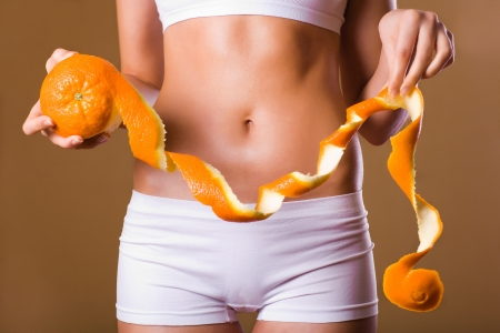 with orange and white body: waist, abdomen and orange in hand cellulite liposuction woman weight loss control concept, close up Stock Photo