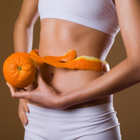 waist, abdomen and orange in hand cellulite liposuction woman weight loss control concept, close up Stock Photo