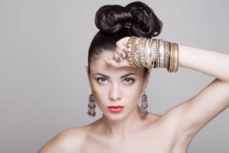 fashion model with hairstyle and jewelry, studio shot