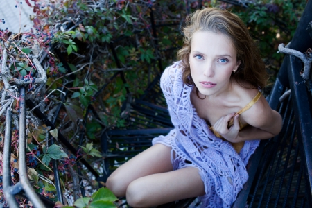 Fashion portrait of young sensual woman in garden  sitting on the stairs Stock Photo