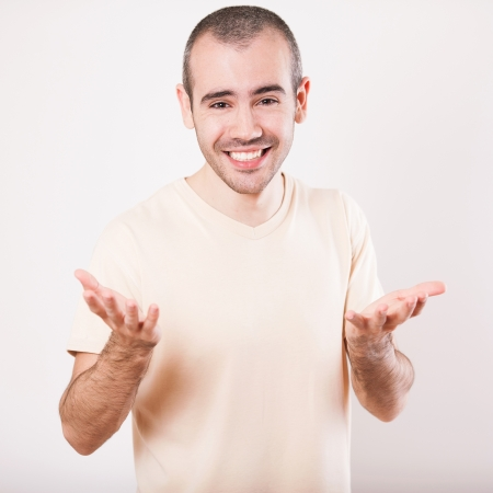 Happy smiling man on shirt presenting and showing something on white background