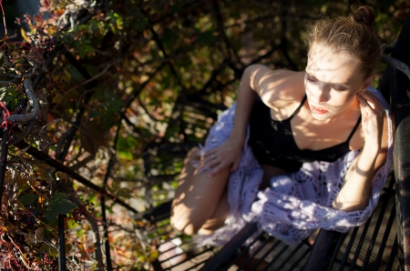 Fashion portrait of young sensual woman in garden sitting on the stairs