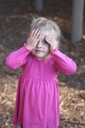 Young girl playing Peek a boo Imagens