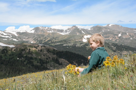 Boy sits with wildflowers on mountain. Imagens