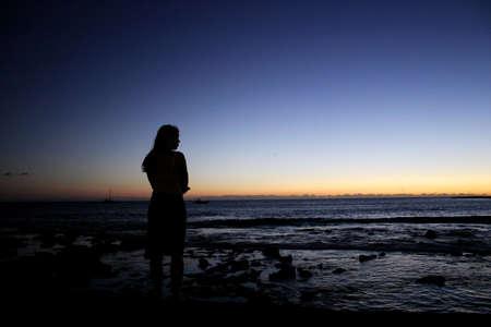 mujeres tristes: chica busca a la puesta del sol sobre el oc�ano